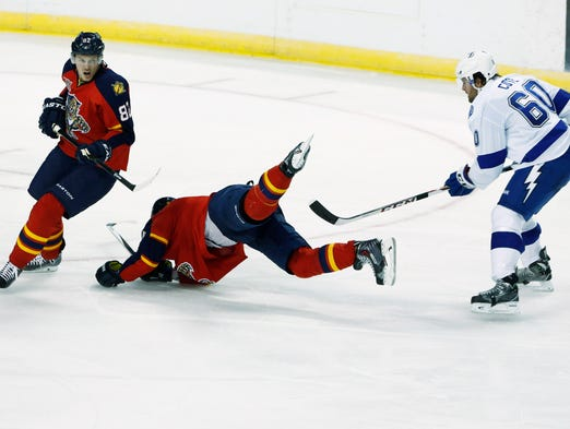 Tampa Bay Lightning defenseman Jean-Philippe Cote (60) upends Florida Panthers defenseman Dmitry Kulikov (center) as center Tomas Kopecky (82) looks for the puck in the second period at the BB&T Center.