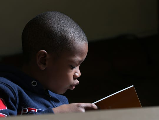 Jayden Mason, a first grader, reads during class at