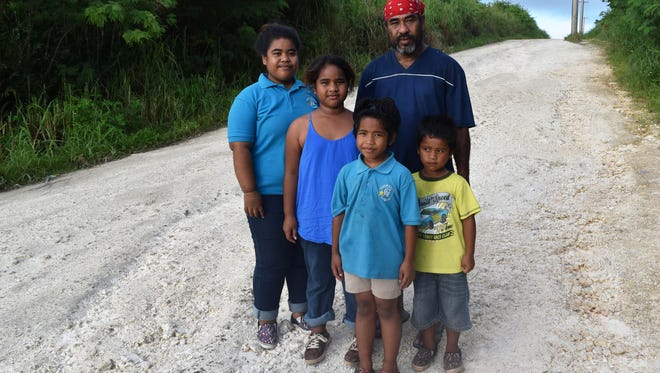 Gregory Erakilur, wearing a red bandanna, is joined by his children, from left, Maliah Mario, Richelle Erakilur, Raejean Erakilur and McArthur Erakilur, on the Lucas Sablan Boulevard at the Gill Breeze Subdivision in Yigo, on Feb. 7, 2017.