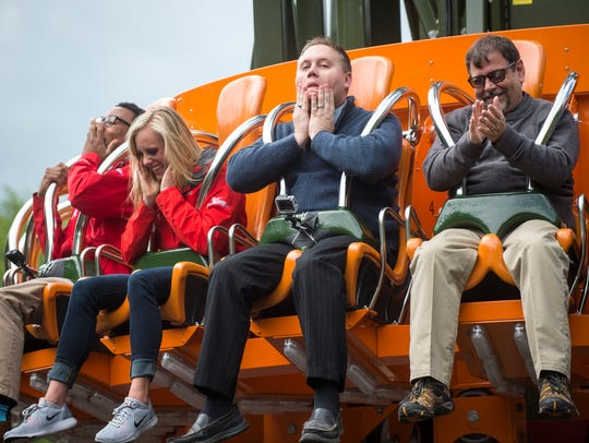 Members of the media react after riding the Drop Line,
