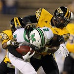 Dylan Bradley, right, brings down former Marshall quarterback Rakeem Cato during a game last season.
