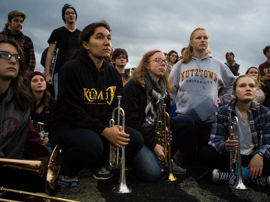 Freshman Grace Weikert, middle, a graduate of Dallastown High School, listens with other band members of Kutztown University Marching Unit to director Daniel Neuenschwander at the end of rehearsal at Andre Reed Stadium on Kutztown University campus on Nov. 18 in Kutztown.