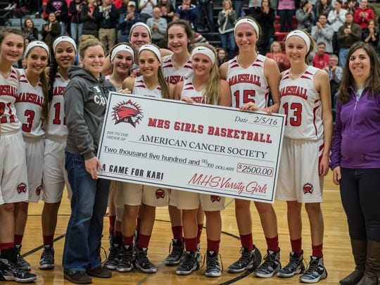 Kari (Searles) Jolink helps present a check to the American Cancer Society on Friday.