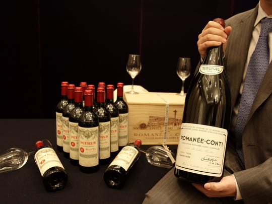 A bottle of Romanee-Conti, considered some of the most expensive in the world, is held during an auction in Hong Kong on Nov. 12, 2008. The late Rehoboth Beach businessman Jay Stein also collected fine wine, some of which will be sold at auction in New York.