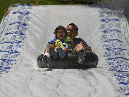 Marcos Villalba (right) helps Ali Ben Lanes, 5, go down a slide during the Walmart Heart Camp for Life at Whiskeytown National Recreation Area.