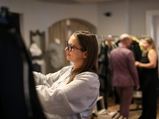 Julie Konikoff looks through the designs of Daniel Wingate, a Tallahassee native and international fashion designer, who brought his clothing line to Hearth & Soul on Thursday, May 17, 2018.