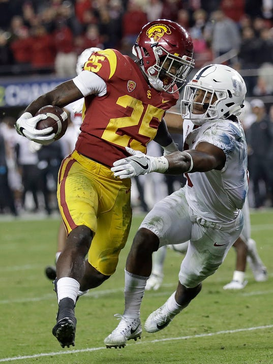 "File- This Dec. 1, 2017, file photo shows Southern California running back Ronald Jones II (25) running past Stanford safety Justin Reid to score a touchdown during the second half of the Pac-12 Conference championship NCAA college football game in Santa Clara, Calif. Jones would rather forget about his last trip home to play a game. So would all of his Trojans teammates who were part of that 2016 season opener in the home stadium of the NFL's Dallas Cowboys, a 52-6 loss to Alabama that was the most lopsided setback in a half-century for the Trojans. ""We've definitely got to get that sick taste out of our mouths,"" Jones said, who is from the Dallas suburb of McKinney. (AP Photo/Marcio Jose Sanchez, File)"