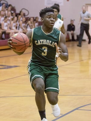 Ja'kobi Jackson (3) drives to the basket during the basketball game between Catholic and Navarre at Navarre High School on Tuesday, December 5, 2017.