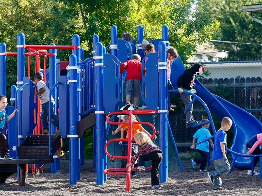 Students play on recess equipment.