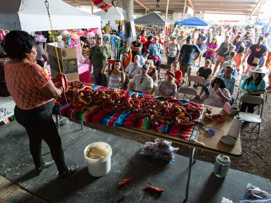 Many gather as Rocio Banuelos provides free chile ristra demonstrations on Saturday, September 2, 2017, during the annual Hatch Chile Festival.