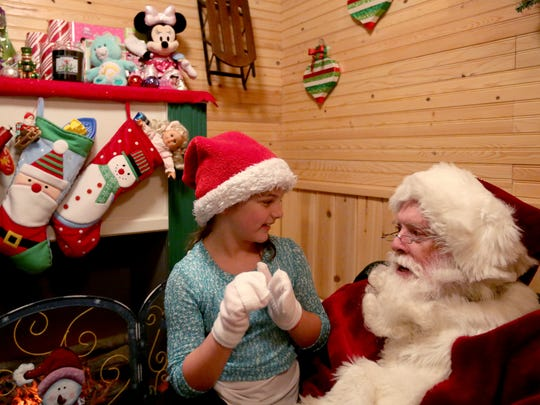 Emma Dougherty, 7, of Salem, tells Santa what she wants for Christmas during the annual Christmas Holiday Lighting Kick Off at Gatti and Gatti Law in Salem on Saturday, Nov. 28, 2015. The display will stay lit every night through New Year's Day, with Santa visits every Thursday - Sunday from 5:30 p.m. to 8 p.m. through Dec. 20.