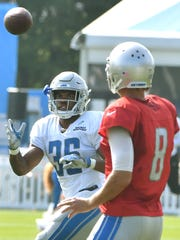 Lions running back Dwayne Washington readies for a reception from quarterback Matt Cassel during Thursday's practice.