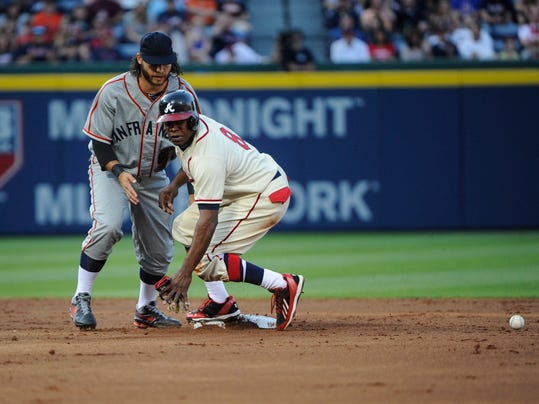 Atlanta Braves' Justin Upton (8) comes up safe at second base after San Francisco Giants shortstop Brandon Crawford could not handle the throw after Evan Gattis reached on a force attempt during the second inning of a baseball game, Saturday, May 3, 2014, in Atlanta. (AP Photo/John Amis)