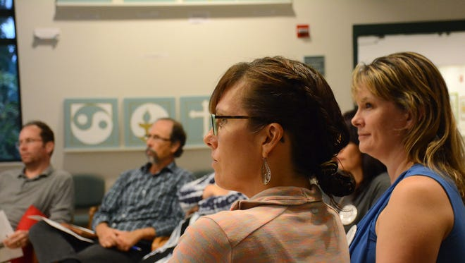 Participants including Heather Desrocher, right, listen to the presenter, family counselor Stacey Brown.