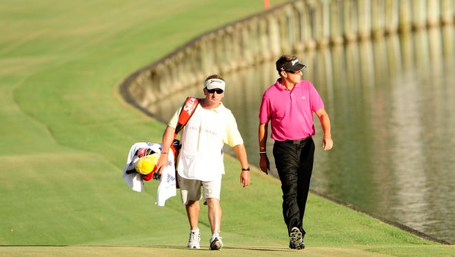 Robert Allenby walks down the 18th fairway with caddie Colin Burwood during the final round of The Players Championship in 2010.