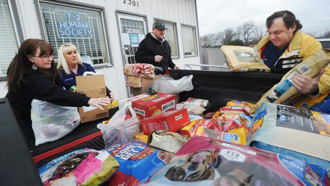 From left, Kay Caffey, Deanna and Cesar Morales and Dr. Keith Robinson unload several hundred pounds of dog and cat food at the Taylor-Jones Humane Society. The doctor held a raffle at his office to raise these donations, and the 4 winning couples will attend a 6-course dinner at his home, cooked by him and his wife. Over 400 pounds of pet food were collected, as well as toys, beds, blankets, litter, collars and leashes, and $700. The other half of donations will go to Rescue the Animals.
