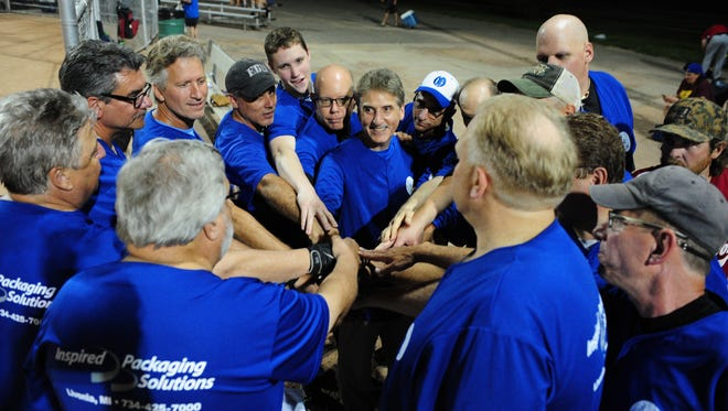 It's all hands in for the Inspired Packaging Solutions softball team before playing July 21 at Claude Allison Park in Redford. The team is in its 40th season.