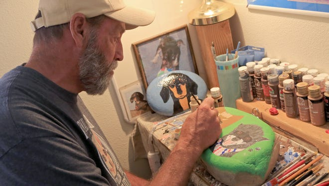 At his home in Washington City, Randy Brown paints the portraits of two dogs who regularly visit the city's Dog Town Park.
