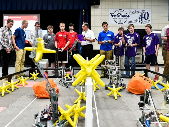 Students gather around one of the makeshift arenas as a Hex robot competition begins in which robots students designed and control attempt to move objects from one side of the arena to the other.