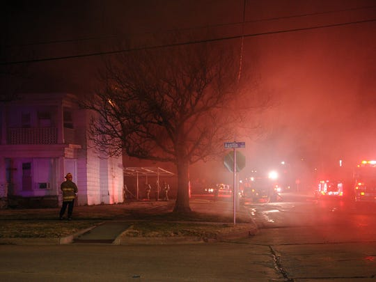 Firefighters work to put out an apartment fire at the 1500 block of Austin Street Monday.
