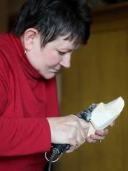 Kristi Schumacher carves a Santa with a Dremel tool.