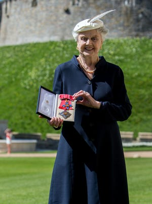 Angela Lansbury poses with her Dame Commander (DBE) medal given to her by Queen Elizabeth II at a ceremony at Windsor Castle on April 15 in Berkshire, England.