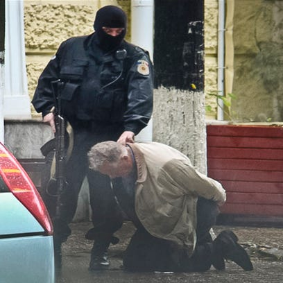 In this June 27, 2011 photo provided by the Moldova General Police Inspectorate, Teodor Chetrus carries a green sack containing a sample of uranium-235 in Chisinau, Moldova.