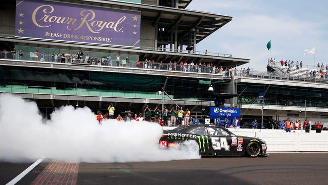 Kyle Busch does a burnout on the front straight after winning the NASCAR Xfinity Series auto race at Indianapolis Motor Speedway, July 25, 2015.