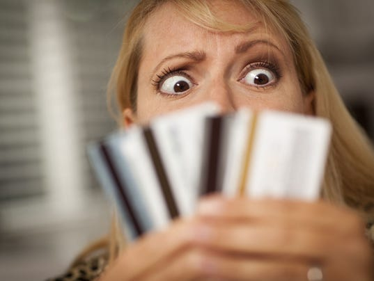 A perplexed woman looking at various credit cards