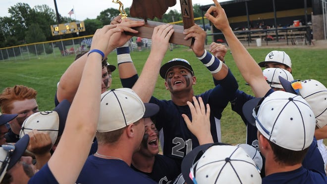 CC senior Anthony Berumen raises the victor's trophy surrounded by his team mates following Monday's Central Catholic sectional championship at Delphi.