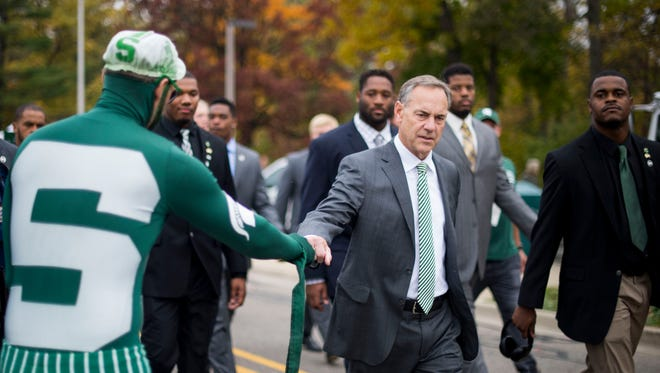 Michigan State Spartans coach Mark Dantonio fist bumps a fan while he walks with players towards Spartan Stadium before their game against Michigan on Saturday, Oct. 29, 2016.