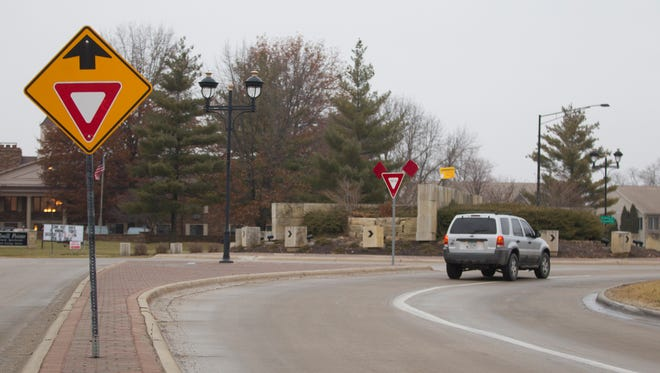 A car passes through the roundabout at First Avenue and Holiday Road in Coralville on Sunday, Dec. 14, 2014. David Scrivner / Iowa City Press-Citizen