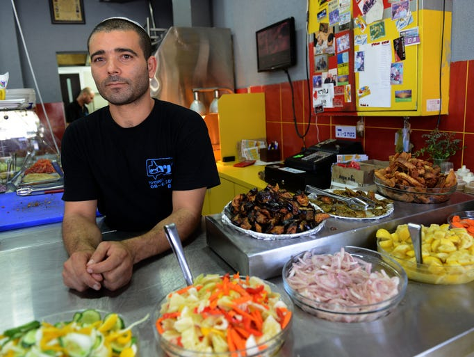 Yisrael Karisi, 35, stands inside his empty restaurant in Ashkelon, Israel. Since the start of the war, Karisi earns about $125 a day compared with close to $1,750 a day because people are afraid to leave home because of the rockets.