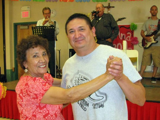 Oralia Tulk takes a twirl on the dance floor with her son Gerardo Gonzales on Sunday during the 67th annual St. Ann Catholic Church Fiesta.