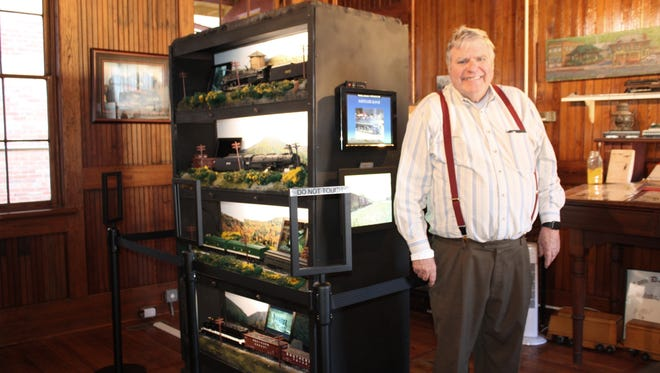 "Fred ""Mac"" McConnel stands beside the train models he donated to the Saluda Historic Depot."