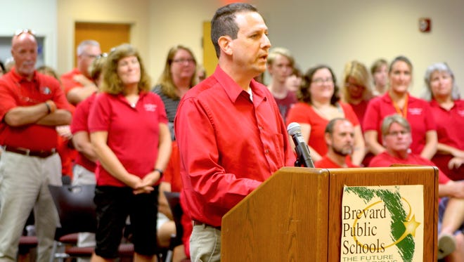 """Brevard County teachers union president Dan Bennett addresses the school board at Tuesday night's meeting. About 100 teachers wearing red joined him to speak against the """"insulting"""" 1 percent raise the school district offered last week."""