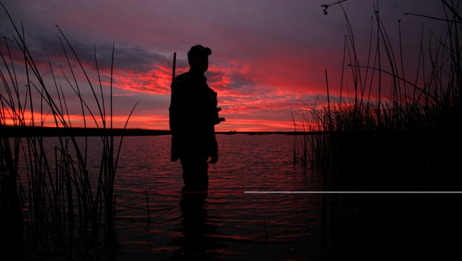 A waterfowl hunter awaits the first flight of the day at dawn on a marsh.