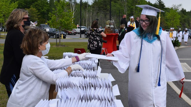 """Graduate Jade Jamison receives her diploma during Sanford High School's """"drive-through"""" commencement ceremony on the SHS campus on Wednesday, June 10."""
