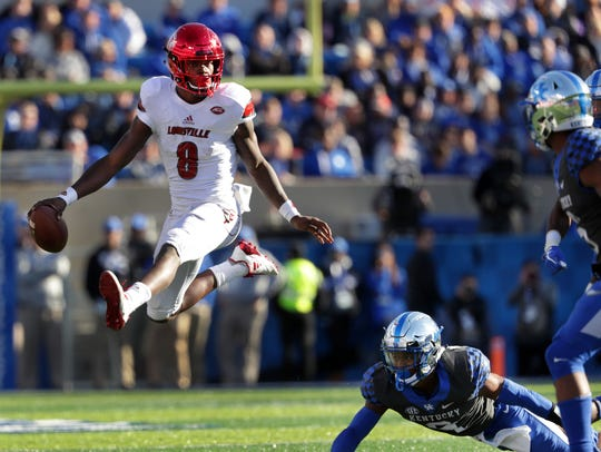Lamar Jackson leaps two UK players during Louisville's 2017 win.