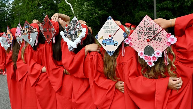 Milford High School graduates show off their mortarboards Saturday morning before graduation exercises.