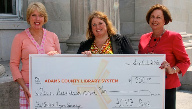 Lauren Muzzy, left, ACNB Bank Vice President/Corporate Relations Officer and Karen B. Arthur, right, ACNB Bank First Vice President/Senior Trust Officer, presented a check for $500 to Karla Trout, Executive Director of the Adams County Library System, for the Fall Science Program.
