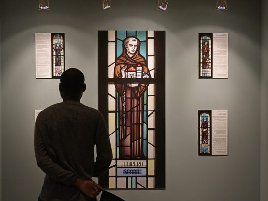 A man looks at an exhibition on Junipero Serra at The
