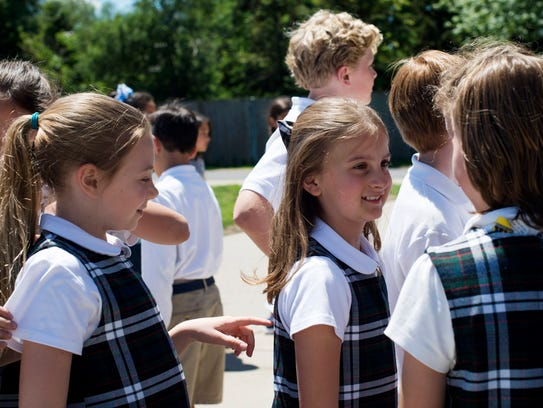 St. Paul Catholic School student Claire Juip, 9, center