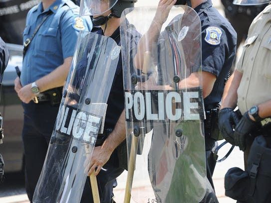 Police officers equipped in riot gear line up during