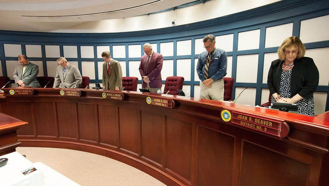 Sussex County Council members stand and recite the 23rd Psalm before Tuesday's council meeting.