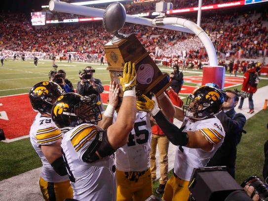Members of the Iowa Hawkeyes football team hoist the