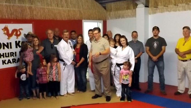 Oni Ken karate owner, Trent Petty, cuts the ribbon while his family, friends, students and members of the Chamber of Commerce watch on Tuesday in Silver City.