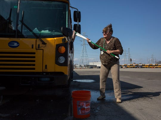 """Veteran school bus driver of 17 years, Brenda Fiedler, 60, of Melvindale washes the front windows of her bus before her route on Wednesday Feb. 28, 2018 in Dearborn. """"Well I don't know, just the fear of being privatized because we can't get the drivers,"""" Fielder said due to the lack of bus drivers."""