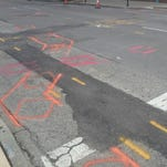 Colorful markings show the approximate location of various underground utilities along Cincinnati's streetcar route.