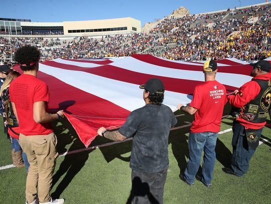Military veterans hold a giant U.S. flag on the field
